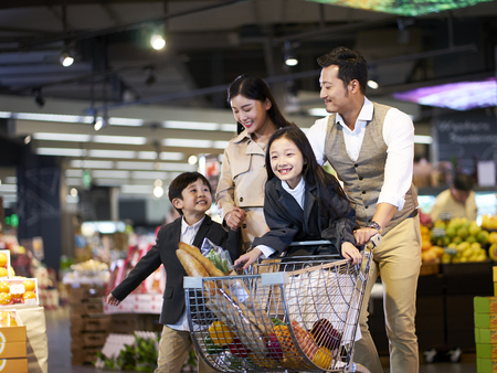 happy asian family with two children shopping in supermarketの写真素材