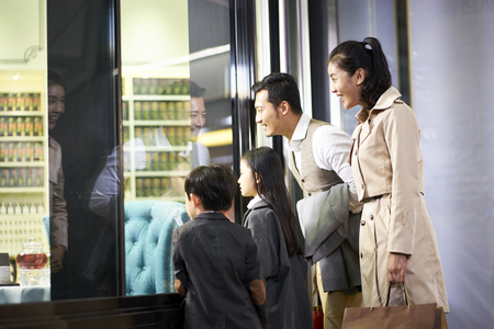 Foto de happy asian family with two children looking into a shop window in shopping mall - Imagen libre de derechos