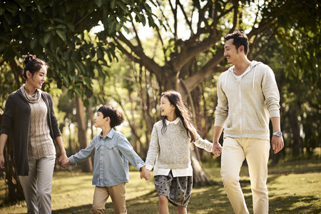 Photo pour asian family with two children walking relaxing in park happy and smiling. - image libre de droit
