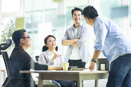 Foto de group of four happy young asian corporate people teammates meeting discussing business in office. - Imagen libre de derechos