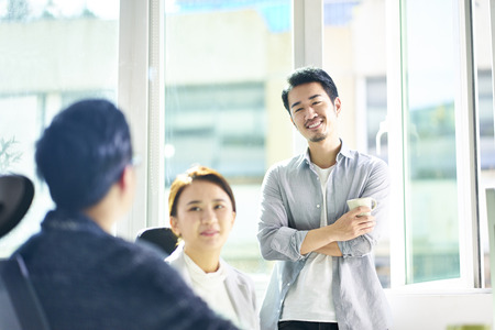 Photo for three young asian men and woman chatting in office, happy and relaxed. - Royalty Free Image