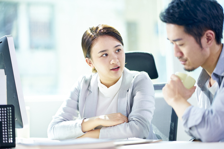 Photo for asian businessman and businesswoman working together in office discussing business plan. - Royalty Free Image