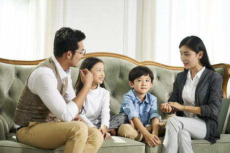 Photo pour young asian parents and two children sitting on couch chatting in  living room at home - image libre de droit