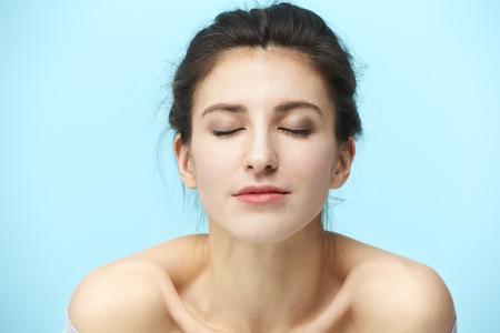 Photo pour head and shoulder portrait of a young caucasian woman isolated on blue background - image libre de droit