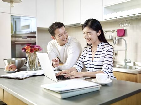 Foto de happy young asian couple working together from home talking discussing using laptop computer in kitchen - Imagen libre de derechos