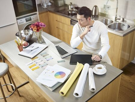 Photo for high angle view of a young asian designer sitting at kitchen counter working on a design using laptop computer and digital pen tablet - Royalty Free Image