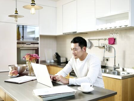 Foto de young asian man working from home sitting at kitchen counter using laptop computer - Imagen libre de derechos