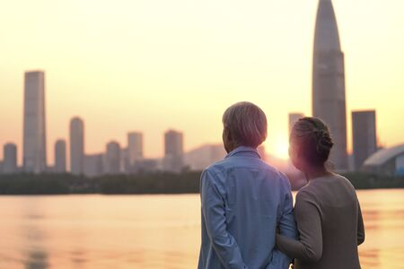Photo for rear view of senior asian couple looking at sunset and city skyline by river - Royalty Free Image
