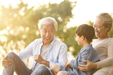 Photo for asian grandson, grandfather and grandmother sitting chatting on grass outdoors in park at dusk - Royalty Free Image