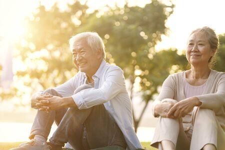 Photo for asian senior couple sitting on grass enjoying sunset outdoors in park - Royalty Free Image