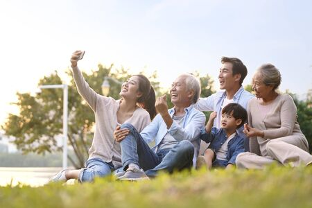 three generation happy asian family sitting on grass taking a selfie using mobile phone outdoors in park