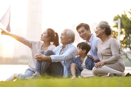 Photo for three generation happy asian family sitting on grass enjoying good time at dusk outdoors in park - Royalty Free Image