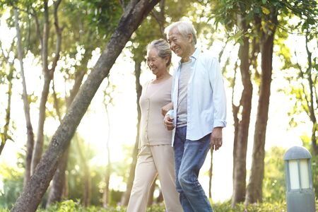 Photo for happy senior asian couple walking talking relaxing outdoors in park - Royalty Free Image