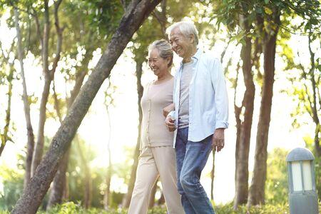 Photo pour happy senior asian couple walking talking relaxing outdoors in park - image libre de droit