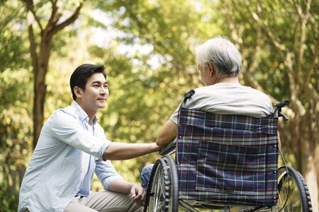 Photo pour asian son talking to and comforting wheelchair bound father - image libre de droit