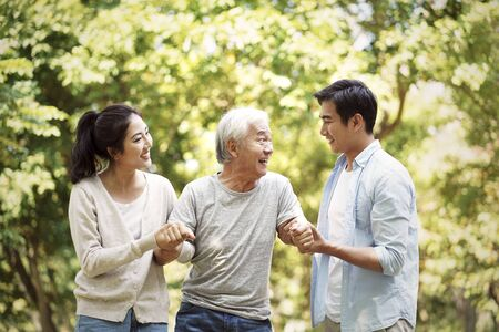 Photo pour young asian man and woman helping senior man stand up and walk - image libre de droit