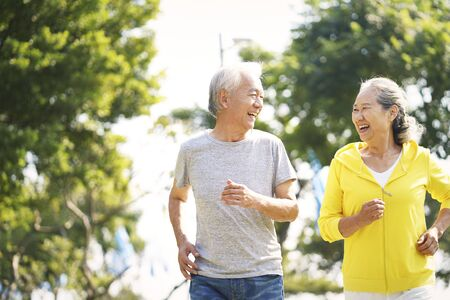 Foto de happy asian old couple jogging running outdoors in park - Imagen libre de derechos