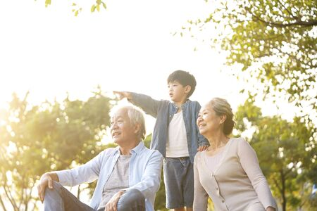 Photo pour asian grandson, grandfather and grandmother sitting chatting on grass outdoors in park at dusk - image libre de droit