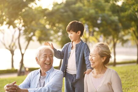Photo pour Asian grandparents and grandson chatting while sitting on grass in park outdoors at dusk - image libre de droit