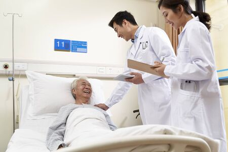 Photo for two young friendly asian doctors talking to senior asian male patient at bedside in hospital - Royalty Free Image