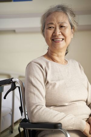 Photo for happy senior asian woman sitting in wheel chair in her room in nursing home, happy and smiling - Royalty Free Image