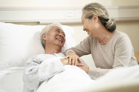 Photo for loving and caring senior asian woman visiting and talking to hospitalized husband at bedside - Royalty Free Image