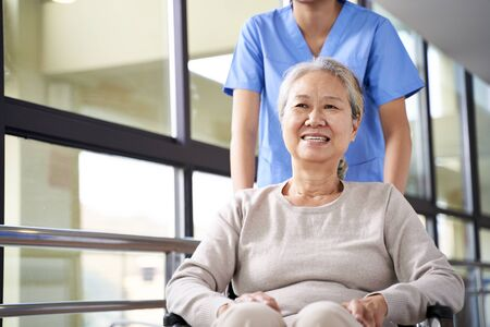 Photo for asian caregiver assisting wheelchair bound senior woman in hallway of nursing home - Royalty Free Image