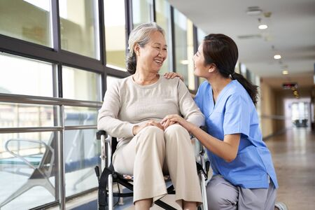 Photo for friendly staff caregiver of nursing home talking to asian senior woman in hallway - Royalty Free Image