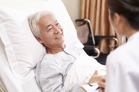 Photo for young asian doctor talking to senior patient at bedside in hosptial ward - Royalty Free Image