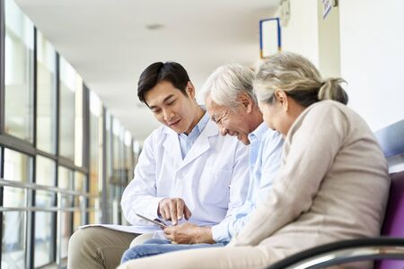 Photo for young asian doctor discussing test result and diagnosis with senior couple patients using digital tablet in hospital hallway - Royalty Free Image