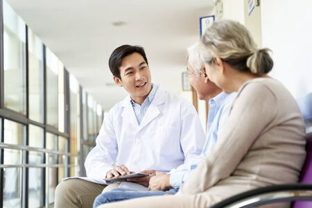 Photo for friendly young asian doctor talking to old couple in hospital hallway - Royalty Free Image