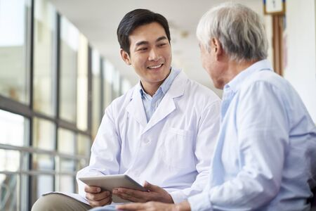 Photo for friendly smiling young asian doctor talking and explaining test result to elderly patient in hospital - Royalty Free Image