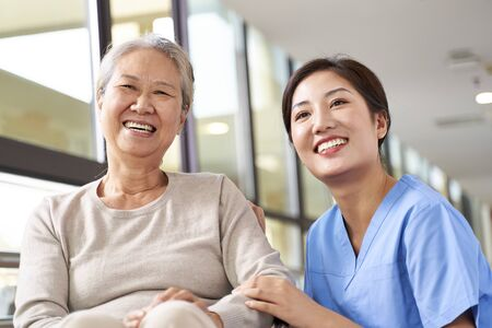 Photo for asian senior woman and her caregiver looking at camera smiling - Royalty Free Image