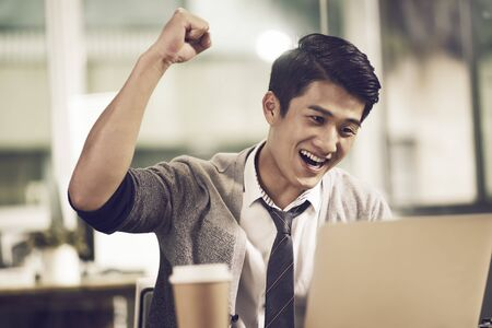 Photo for young asian businessman waving fist celebrating success while looking at laptop computer in office - Royalty Free Image