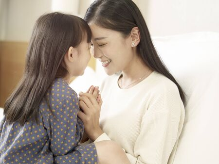 Photo for close-up shot of loving asian mother and cute daughter sitting in bed at home - Royalty Free Image