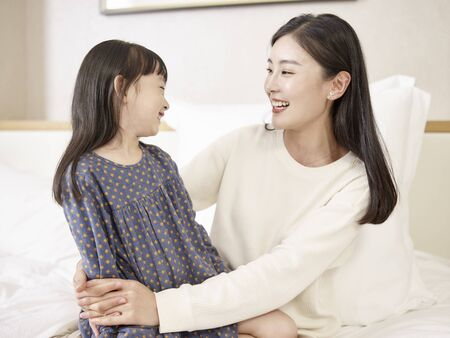 Photo pour young asian mother and elementary age daughter sitting in bed relaxing playing chatting at home - image libre de droit