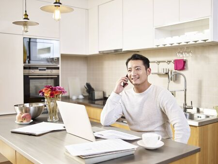 Photo pour young asian business man sitting kitchen counter working at home talking on mobile phone - image libre de droit
