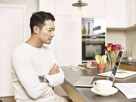 Photo for young asian businessman working from home sitting at kitchen counter looking at laptop computer arms crossed - Royalty Free Image