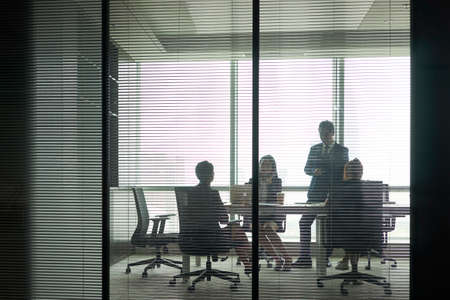 Photo pour through-the-glass shot of a group of business people meeting in conference room - image libre de droit