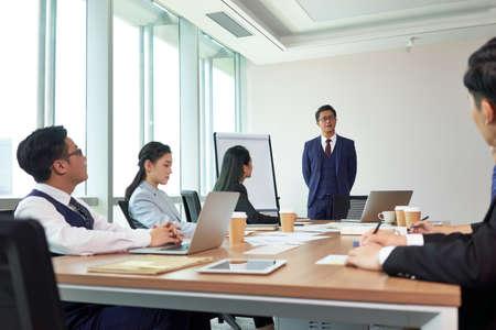 Foto de asian boss delivering a speech during meeting in company conference room - Imagen libre de derechos