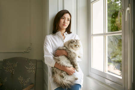 Photo for beautiful young asian woman standing by window at home holding a cat in arms looking depressed and sad - Royalty Free Image
