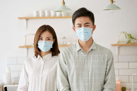 Photo for portrait of a young asian couple wearing mask looking at camera - Royalty Free Image