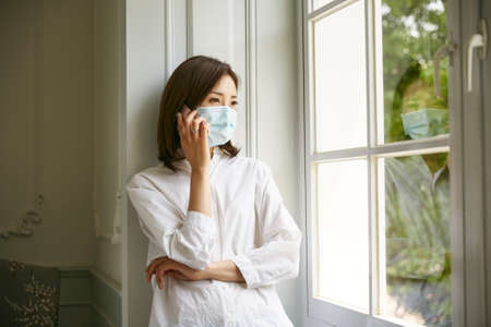Photo for young asian woman in wearing isolation mask standing by window talking on cellphone - Royalty Free Image