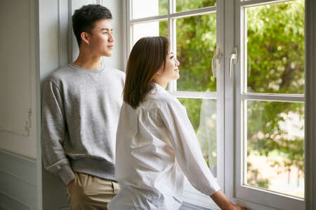 Photo pour young asian couple standing by the window talking chatting during stay at home order - image libre de droit