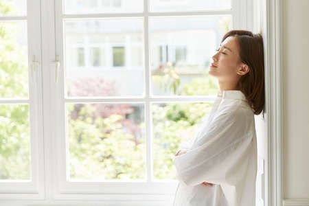 Photo for beautiful young asian woman standing by window - Royalty Free Image