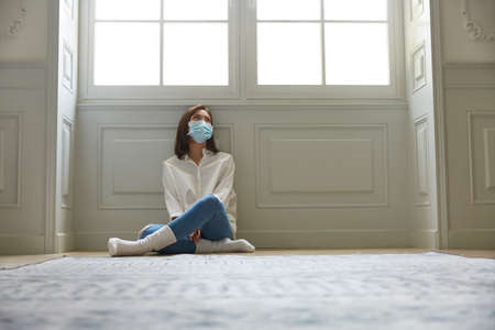 Photo for young asian woman in quarantine at home wearing facial mask sitting on floor legs crossed looking sad and depressed - Royalty Free Image