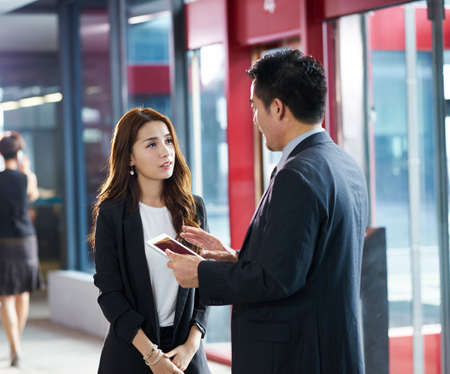 Photo for asian business man and woman standing and talking in company elevator hall using digital tablet - Royalty Free Image