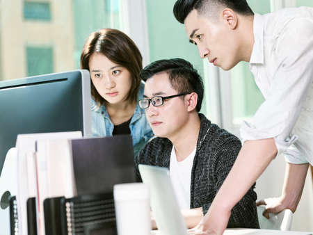 Photo for team of three young entrepreneurs analyzing data in office using desktop computer - Royalty Free Image