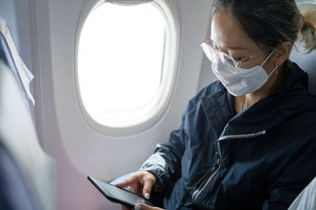 Photo for asian woman female passenger sitting in cabin of airplane reading ebook using e-reader - Royalty Free Image