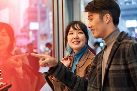 Photo for loving young asian couple looking at shop window and talking happy and smiling - Royalty Free Image